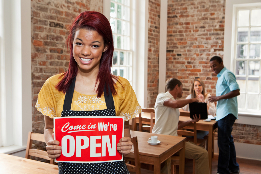 Waitress in cafe holding open sign