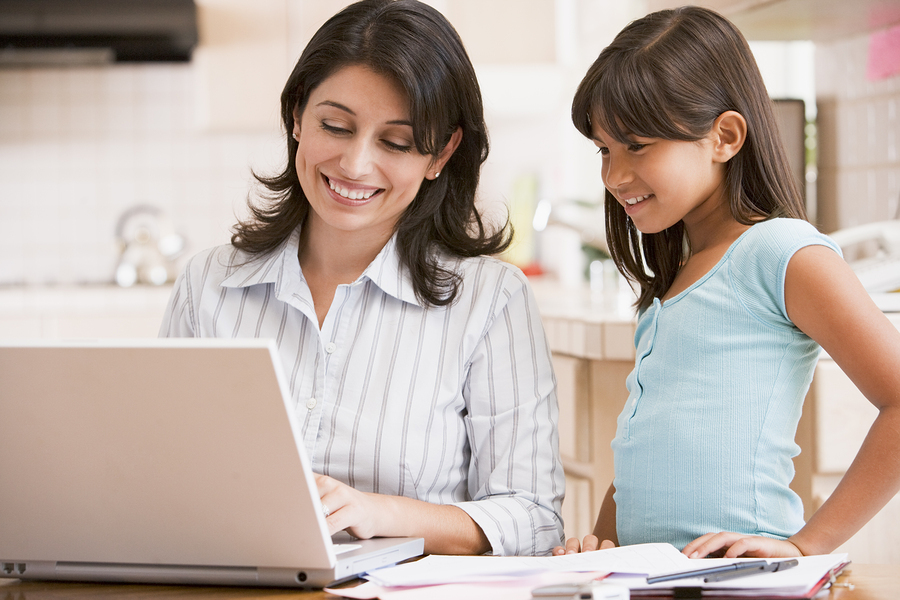 Woman And Young Girl In Kitchen With Laptop And Paperwork Smilin